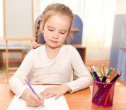 Cute little girl is writing at the desk Royalty Free Stock Photo