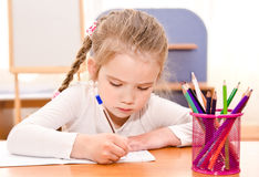 Cute little girl is writing at the desk. In preschool Stock Photo