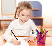 Cute little girl is writing at the desk Stock Photography
