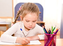 Cute little girl is writing at the desk Royalty Free Stock Photography