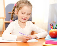 Cute little girl is writing at the desk  in preschool Royalty Free Stock Photography