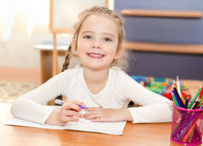 Cute little girl is writing at the desk  in preschool. Cute smiling little girl is writing at the desk  in preschool Royalty Free Stock Images