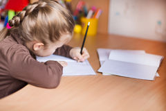 Cute little girl writing her homework Stock Images
