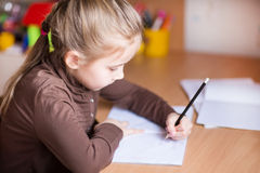 Cute little girl writing her homework Royalty Free Stock Photos