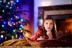 Cute little girl writing a letter to Santa by a fireplace on Christmas Royalty Free Stock Photo