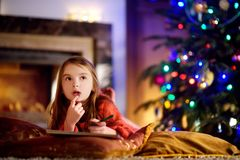 Cute little girl writing a letter to Santa by a fireplace on Christmas Stock Image