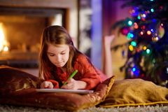 Cute little girl writing a letter to Santa by a fireplace on Christmas Stock Photos