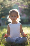 Cute little girl 4 - 5 years old meditating at green summer park in lotus pose. Close-up Royalty Free Stock Image