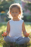 Cute little girl 4 - 5 years old meditating at green summer park in lotus pose. Close-up Stock Photos