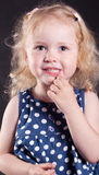 Cute little girl 3 years old  thought looking at the camera. Cute little girl 3 years thought looking at the camera. On a dark background Royalty Free Stock Photos