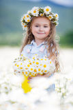 Cute little girl with yellow bucket white daisies. Beautiful little girl with long curly blond hair,cute smile,in a light blue denim overalls,a white wreath of Stock Images