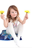 Cute little girl with yellow daisies isolated. Cute little girl sitting on a pillow and holding yellow daisies Royalty Free Stock Photo