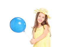 Cute little girl in yellow dress holding a blue balloon Royalty Free Stock Images