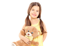 Cute little girl in yellow dress holding a teddy bear Stock Photos