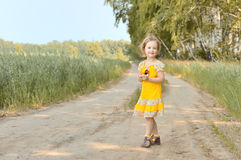 Cute little girl in yellow dress on rural road Royalty Free Stock Photography
