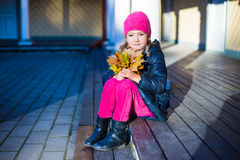 Cute little girl with yellow leaves sitting on the porch Royalty Free Stock Image