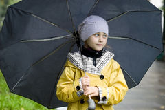 Cute little girl in a yellow raincoat Royalty Free Stock Photo