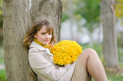 Cute little girl with yellow roses against a tree Stock Photography