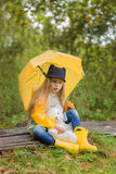 Cute little girl with a yellow umbrella sits on a path in the forest with her favorite toy Royalty Free Stock Photography