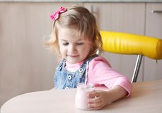 Cute little girl with yogurt. At home Stock Photos