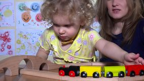 Cute little girl with young mother pushing toy train locomotive on railway. Handheld steadycam flycam movement shot stock video