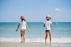Cute little girls on the beach stock images