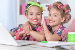 Cute little girls beautifying themselves. Two cute little girls sitting at table with laptop and beautifying themselves Royalty Free Stock Images