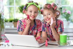 Cute little girls beautifying themselves. Two cute little girls sitting at table with laptop and beautifying themselves Stock Photo