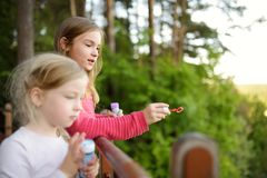 Cute little girls blowing soap bubbles on a sunset outdoors on beautiful summer day royalty free stock images