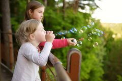 Cute little girls blowing soap bubbles on a sunset outdoors on beautiful summer day royalty free stock photos