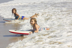 Cute little girls boogie boarding in the ocean waves Stock Photography