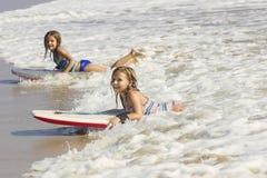 Cute little girls boogie boarding in the ocean waves. Sideview of two cute little girls boarding and playing in the ocean waves Stock Photography