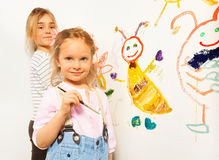 Cute little girls with brushes drawing funny bugs Stock Photography