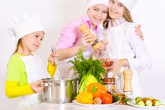 Cute little girls in chef`s hats and aprons preparing dinner in. The kitchen at home Stock Images