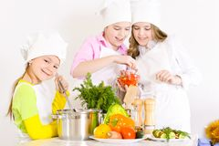 Cute little girls in chef`s hats and aprons preparing dinner in. The kitchen at home Royalty Free Stock Photography