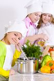 Cute little girls in chef`s hats and aprons preparing dinner in. The kitchen at home Royalty Free Stock Images