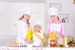 Cute little girls in chef`s hats and aprons preparing dough in t. He kitchen at home Royalty Free Stock Image