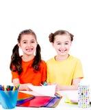 Cute little girls in colourful t-shirt cut scissor cardboard. Stock Image