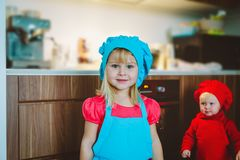 Cute little girls cooking in kitchen interior. Little helpers royalty free stock photography