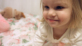 Cute little girls on the couch with floral print Stock Photos