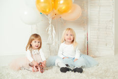Cute little girls in dresses playing together in light room. Happy birthday concept. stock photography