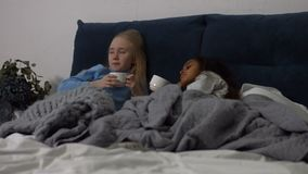Cute little girls drinking tea in bed and chatting stock video footage