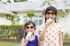 Cute little Girls Eating Ice Cream before their house stock images