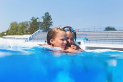 Cute little girls enjoying in pool stock photography