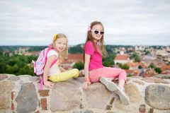 Cute little girls enjoying a view of Vilnius city from the Gediminas hill. Exploring tourist attractions with kids stock images