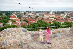 Cute little girls enjoying a view of Vilnius city from the Gediminas hill. Exploring tourist attractions with kids royalty free stock images