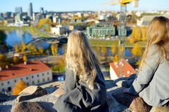 Cute little girls enjoying a view of Vilnius city from the Gediminas hill. Exploring tourist attractions with kids. Cute little girls enjoying a view of Vilnius stock images