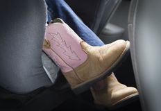 Cute little girls feet in brown and pink cowboy boots. Royalty Free Stock Images