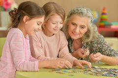 Little girls with grandmother collecting puzzles. Cute little girls with grandmother collecting puzzles together Stock Photos