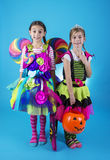 Cute little girls in Halloween costumes ready to go trick or treating. Two cute kids dressed in Halloween costume going trick or treating. Isolated on a bright Stock Image